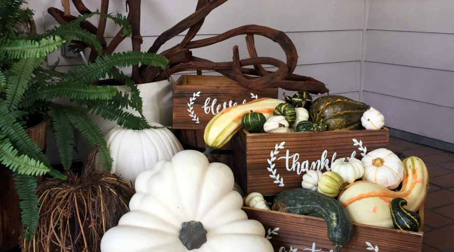 white pumpkins and faux gourds placed on a fall entranceway